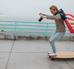 Guy doing longboard trick and wearing flag